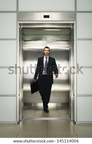 Front view of middle aged businessman with briefcase coming out from elevator - stock photo