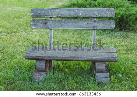Front View Of Old Handmade Wooden Bench Standing On Lawn In The Park Or  Garden Near