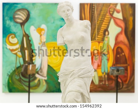 front view of replica of Venus de Milo statue in an art gallery with colorful paintings displayed on walls - stock photo