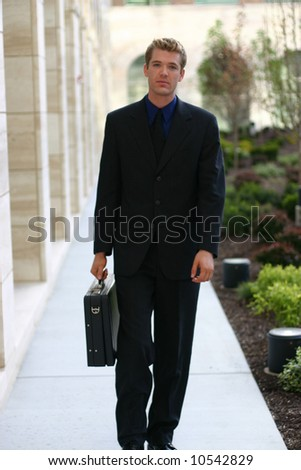 front view of single white young businessman with blond hair and blue eyes wearing suit carrying briefcase walking towards camera - stock photo