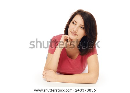 Front view of smiling beautiful woman lying on the floor over white background and looking to the side at blank copy space - stock photo
