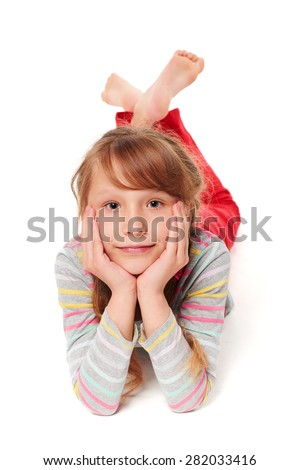 Front view of smiling child girl lying on stomach on the floor with head in hands, over white background  - stock photo