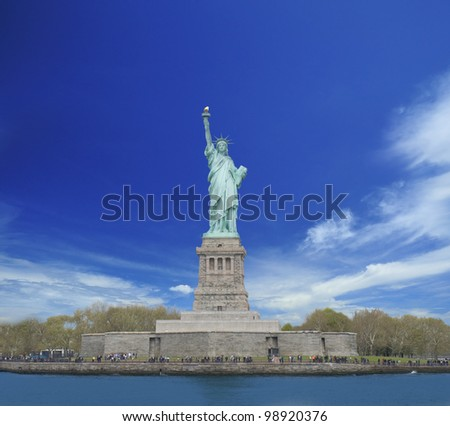 Front view of Statue of Liberty with cloudy blue sky in background - stock photo