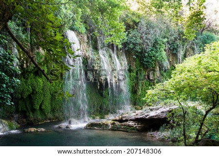 Front view of streaming waterfall with foams in deep forest.