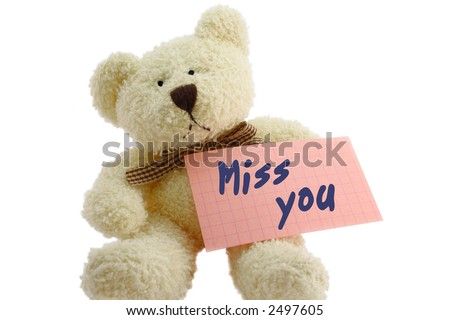"Front view of teddy bear toy with ""Miss you"" note, isolated on white background"