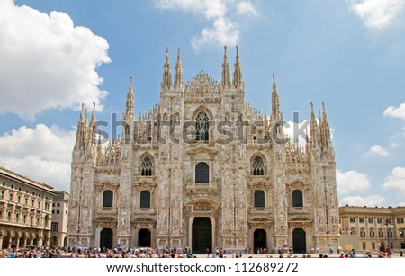 Front view of the Duomo di Milano in Milan, Italy, on a sunny summer day with clouds - stock photo