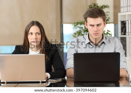 Front view of two angry businesspeople using computers disputing at workplace and looking sideways each other with envy - stock photo