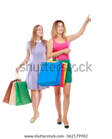 front view of two girls walking with shopping bags.  Isolated over white background.  - stock photo