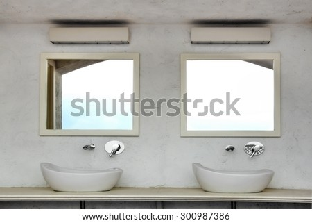Front View Of Two Outdoor Located Sinks With Modern Faucets On A Marble Table Top And Two  Mirror On The Concrete Wall - stock photo