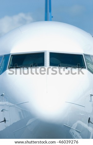 Front view of white passenger airplane with ground equipment reflected in the hull. - stock photo