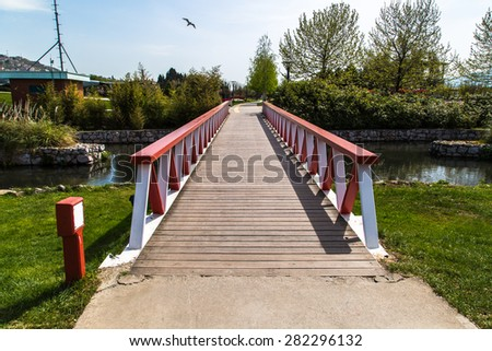Front view of wooden bridge with red and white railing on the river among lush field. - stock photo