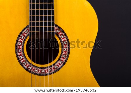 Front view of wooden classical acoustic guitar over black background. - stock photo