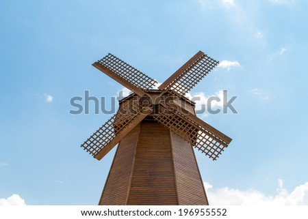 Front view of wooden windmill on cloudy sky. - stock photo