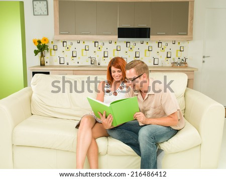 front view of young caucasian man and woman sitting on sofa, reading book together and smiling - stock photo
