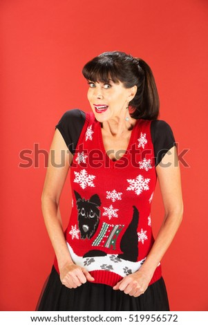 Front view on excited single woman showing off her ugly Christmas theme sweater over red background