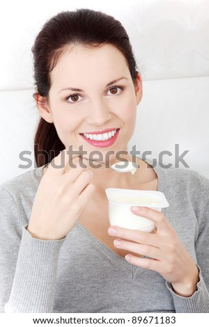 Front view portrait of a beautiful young smiling woman holding a small spoon of yogurt next to her lips. - stock photo