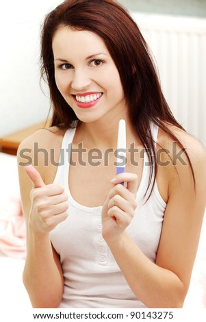 Front view portrait of a beautiful young smiling woman sitting on a bed, showing the pregnancy test and giving a thumb-up. - stock photo