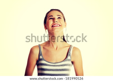 Front view portrait of a smiling young female caucasian teen looking up - stock photo