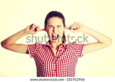 Front view portrait of a young angry female caucasian teen clogging her ears and shouting, on white.