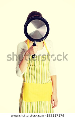 Front view portrait of a young smiling caucasian female teen dressed in apron, holding a frying pan in front of her face, on white.