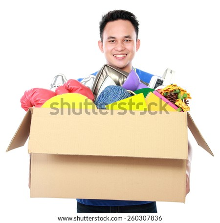 front view portrait of handsome young man carrying box full of stuff on white background