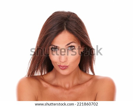 Front view portrait of pretty adult female with nude shoulders for beauty headshot looking at camera with funny face on isolated studio - stock photo