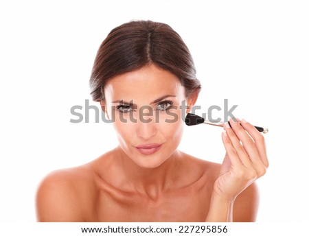 Front view portrait of pretty latin woman applying make up with nude shoulders while looking at camera on isolated studio - stock photo
