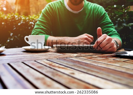 Front view young man sitting at the table with cup of coffee, digital tablet and smart phone, man's hands typing message on touch screen tablet while sitting on balcony terrace with plants, flare - stock photo