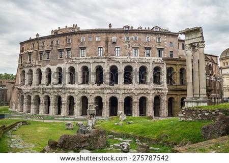 Front wide angle view of Theatre of Marcellus ruins in Rome city centre, Italy, with cloudy sky in the background. - stock photo