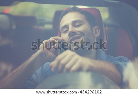 Front window view handsome young man talking on mobile phone while driving his car . Risky, reckless driver bad habits. Traffic safety rule violation lack of attention concept - stock photo
