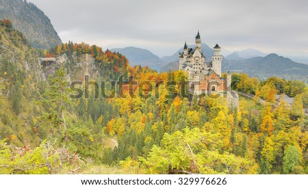 Frontal Facade of fairytale Schloss Neuschwanstein ( New Swan Stone Castle ) perched on a cliff surrounded by autumn colors during cloudy and gloomy sunset ~ Beautiful landscape of Bavaria Germany  - stock photo