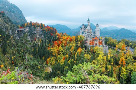 Frontal Facade of fairytale Schloss Neuschwanstein ( New Swan Stone Castle ) perched on a cliff surrounded by colorful autumn foliage on a cloudy gloomy day ~ Beautiful landscape of Bavaria Germany - stock photo