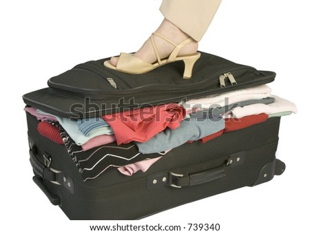 frontal shot of suitcase with female foot pressing lid shut