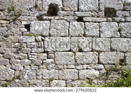 Frontal view of an old stone wall. Medieval Wall consumed by time. Concept image - stock photo
