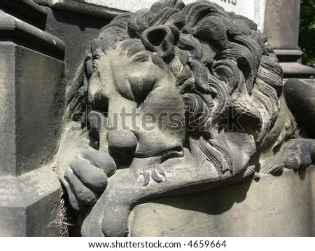 frontal view of craved sleeping lion on grave