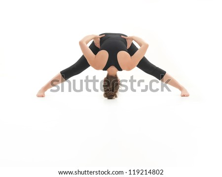 frontal view of stretching yoga posture, by young woman, dressed in blak on white background - stock photo
