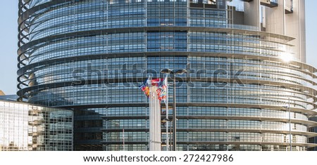 Frontal view of The European Parliament building in Strasbourg, France with flags waving on a spring evening - stock photo