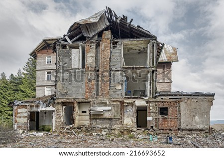 Frontal view on demolished multilevel building with heaps of rubble in front - stock photo