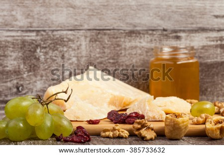 Frontal view on grapes, nuts, honey and fruits on wooden background in studio shooting. Healthy style of life