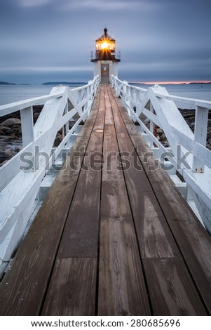 Frontal view over wooden bridge with wide perspective on Marshall Point Lighthouse near small village Port Clyde in Maine, USA. - stock photo