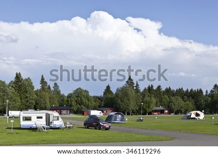 FROSON, SWEDEN ON AUGUST 07. View of a camping, caravans, car and tents on August 07, 2015 in Froson, Sweden. Clouds and showers in the background. Red cabins along a pathway.
