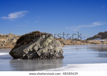 Frosted alpine lake in autumn, with skyline mountains background, Valle Brembana, Italy) - stock photo