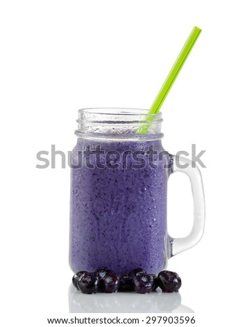 Frosted blueberry shake in jar glass with whole berries and green straw isolated on white with reflection. - stock photo