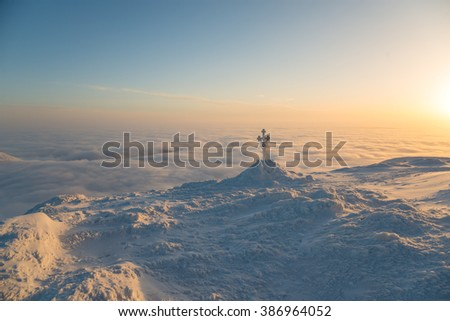 Frosted cross against cloudscape. Morning scene in mountains.