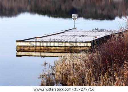 frosted dock at waters edge in fall season - stock photo