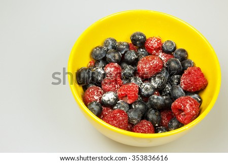 Frosted fruits of highbush bluberyy and raspberries in yellow bowl isolated on white background.Close,horizontal view.