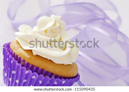 Frosted vanilla cupcake in polka dot wrapper with swirls of lavender chiffon ribbon as background.  Macro with shallow dof.