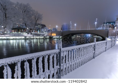 Frosty fence and Tammerkoski river in the center of Tampere, Finland in a wintry landscape - stock photo