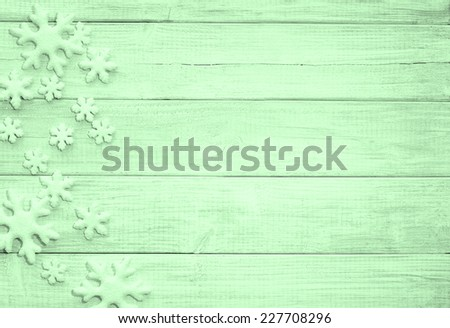 Frosty Snowflakes on Rustic Wood Board Background with empty room or space for copy, text, your words. Horizontal green tone, looking down - stock photo
