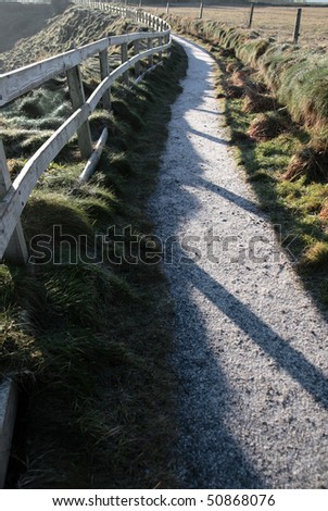 frosty winters view at ballybunion cliffside walk with atlantic view and fence shadows - stock photo